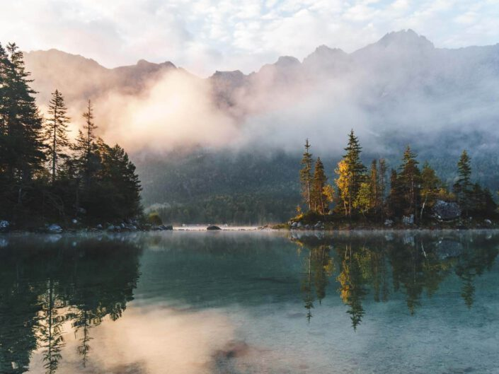 Lake Eibsee in Germany during a foggy sunrise with large mountains in the back.