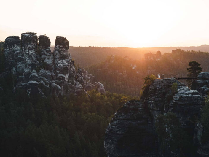 Sunrise at Saxon Switzerland with massive rocks and a girl as scale.