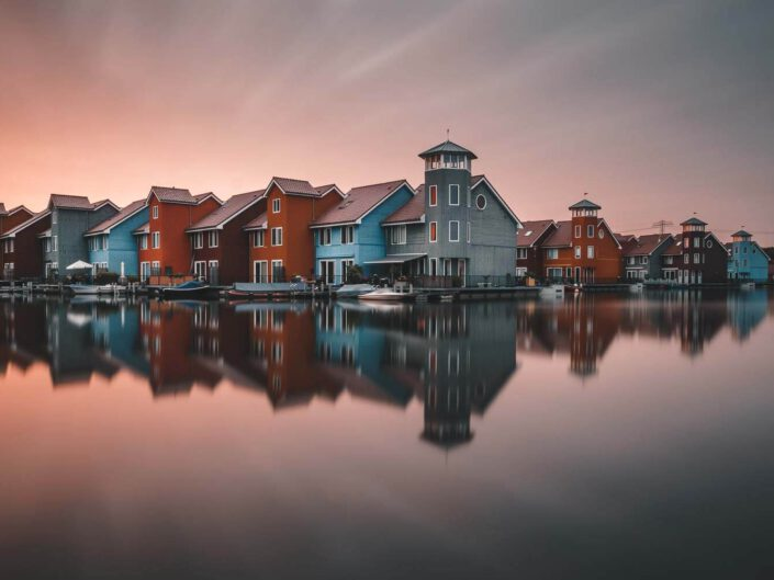 Colourful houses of Reitdiephaven in Groningen during sunset with reflections, Netherlands.