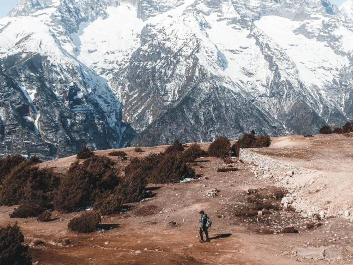 Hiker in front of a massive mountain ridge of the himalayas, Nepal.