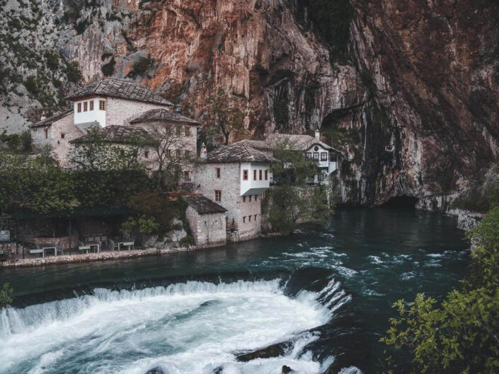Some houses built into rocks next to a river in Blagaj, Bosnia.